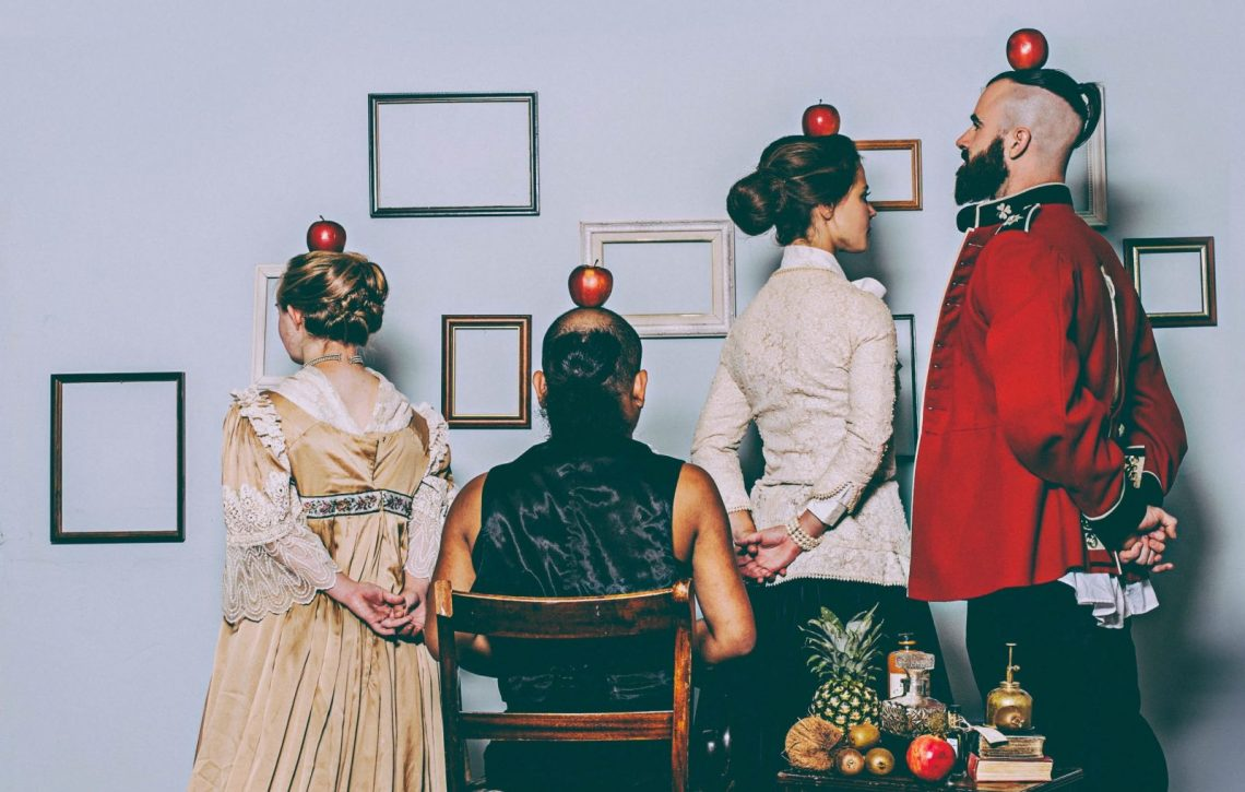 Photo from Stopgap's 2014 production, Exhibition. A group of four dancers are facing a wall hung with empty picture frames, with their backs to the camera. They are dressed in 19th-century style costumes and each balancing a apple on their head. In the foreground a small table with books, bottles, a pineapple, and apple and some kiwi fruit.