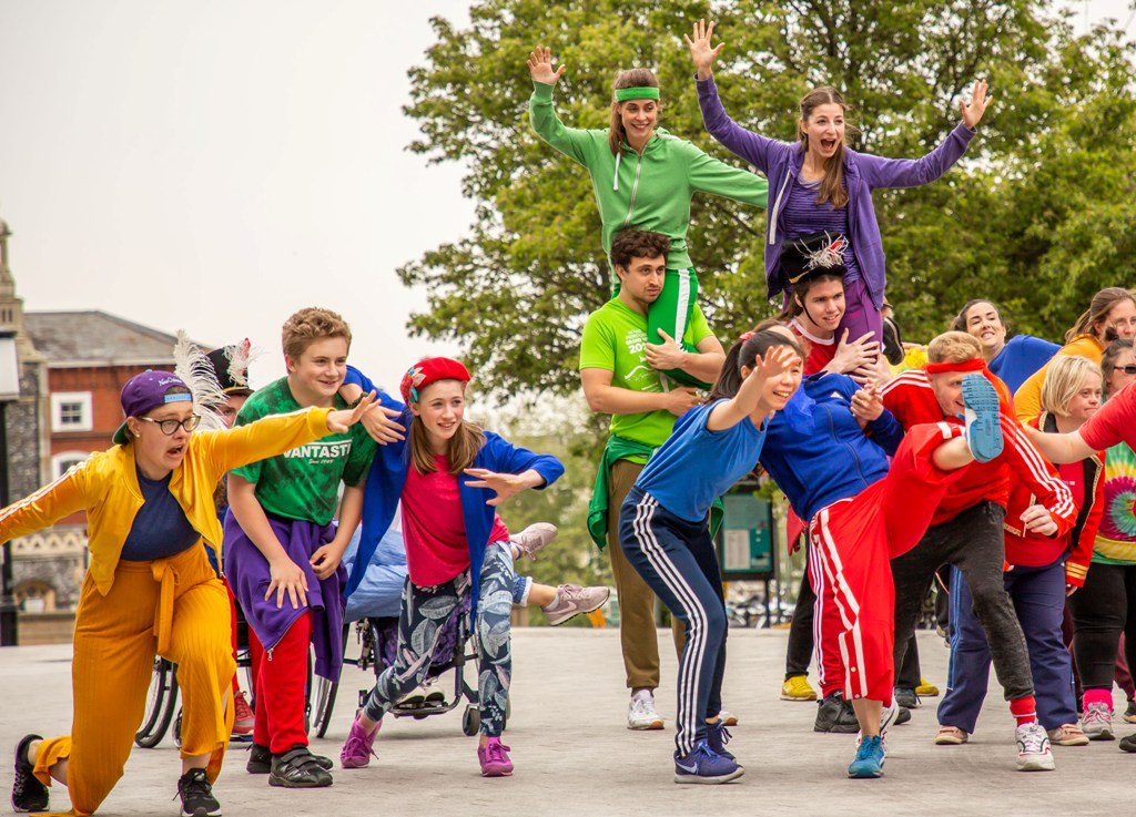 Performance photo of Frippery. A group of young community performers, dressed in colourful tops and trousers, are standing in a row facing the camera, joyfully cheering at something in front of them. Some are throwing their arms forward and one of them is kicking their leg high. Behind them, two male Stopgap dancers carry two of their female colleagues on their shoulders. They are cheering and smiling as well. Photo by Mary Doggett.