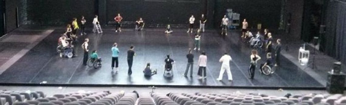 A photo of a group of dancers forming a circle on a stage, taken from high up in the auditorium