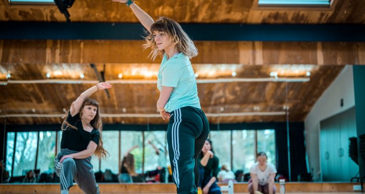 Photo of two female standing dancers with long hair, wearing t-shirts and jogging bootoms with side stripes dancing in the studio.