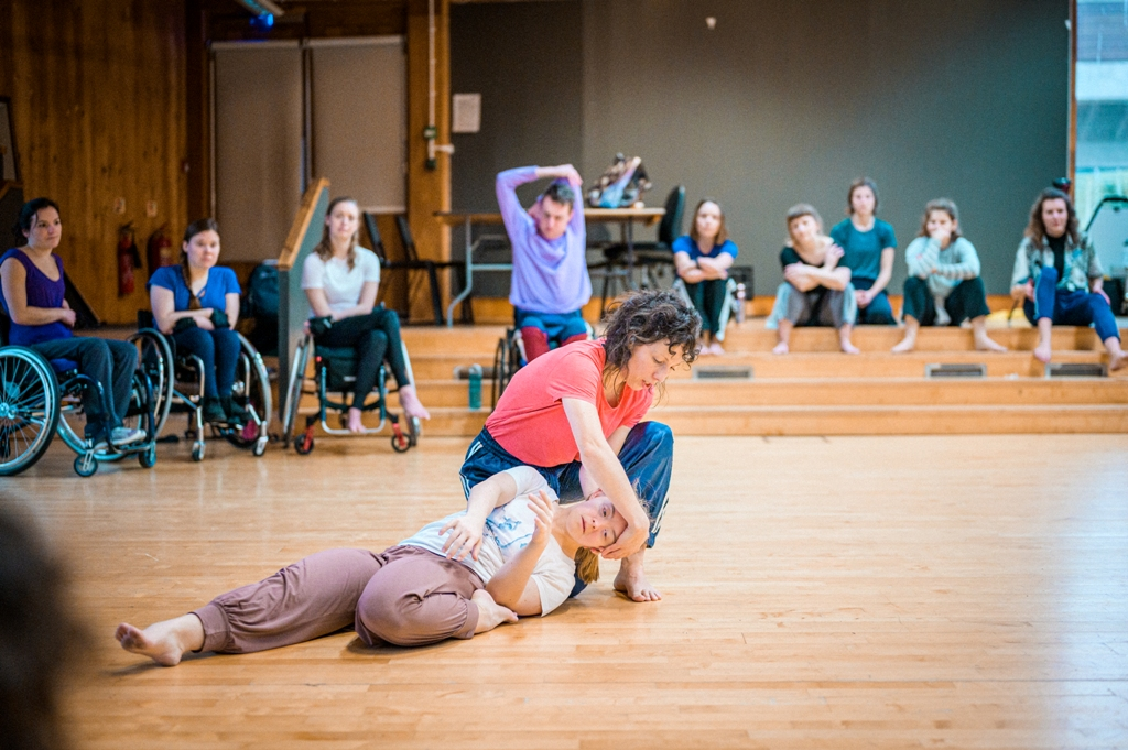 Lucy dancing with Hannah, a learning disabled professional dance artist. Hannah is lying on the wooden studio floor on her back, her left leg tucked in. Lucy is kneeling beside Hannah's head, gently cradling it in her right hand so that it is lifted off the floor. In the background, other company dancers, sitting in wheelchairs or on steps, are observing. Photo by Chris Parkes.
