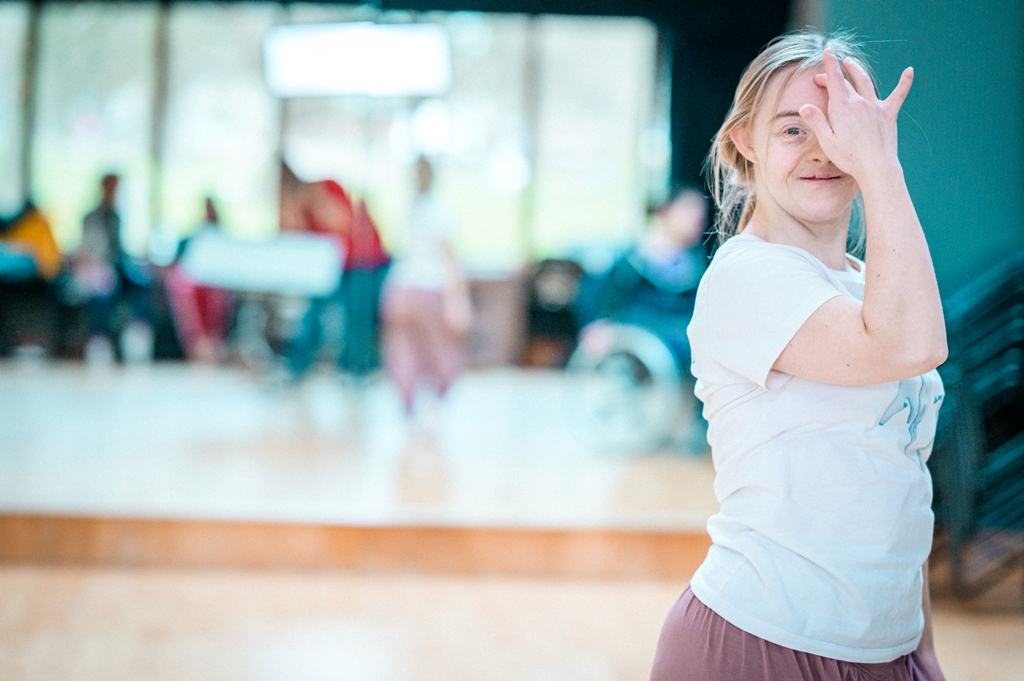 A photo of Hannah, a learning disabled professional dance artist, smiling at the camera. She is in the far right of the image and it cuts off above her waist. Hannah has one hand raised to her face; covering half with one finger resting gently on her forehead. The background is blurred but it's a bright studio space.