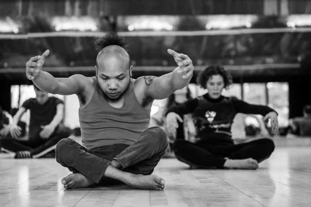 Black and white photo of Nadenh and Amy, two members of the Frock cast, sitting cross-legged on the wooden floor of the dance studio, contracting their upper bodies with arms reaching forward and gaze directed to the floor. The focus is on Nadenh, Amy and other dancers in the background are blurred. Photo by Chris Parkes.