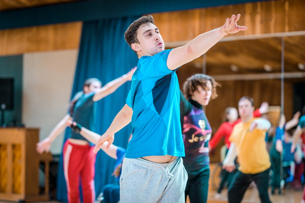 Christian dancing in the studio. Dressed in a blue top and grey jogging bottoms, he is twisting his upper body, throwing his right arm forward, breathing out from puffed cheeks, his gaze following his hand. The left arm is extended behind him. Other dancers are moving in the background behind him. They are blurred, and some are reflected in the studio mirror. Photo by Chris Parkes.