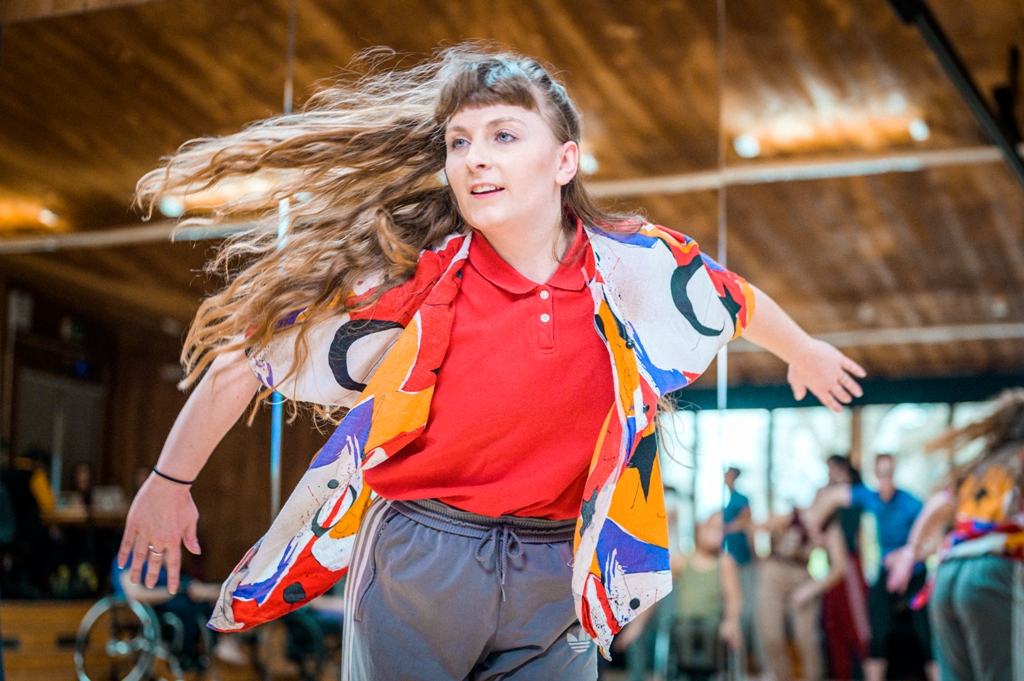 Alice Shepperson dancing in the studio. She is wearing a colourful, floaty, short-sleeved open shirt over a red polo shirt and grey trousers. She pushes her arms back and her long, wavy, light brown hair is being whipped around by her movement. Photo by Chris Parkes.