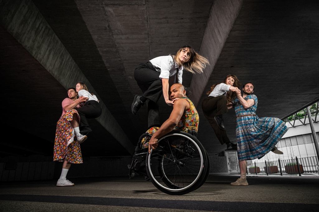 A scene from Frock, photographed in an underpass. In the centre, KJ is climbing on top of Nadenh, who is sitting in his wheelchair. They are flanked to the left and right by couples of a male and a female dancer each. All the male dancers are wearing colourful, patterned dresses; all female dancers are wearing black trousers and white shirts. Photo: Chris Parkes.
