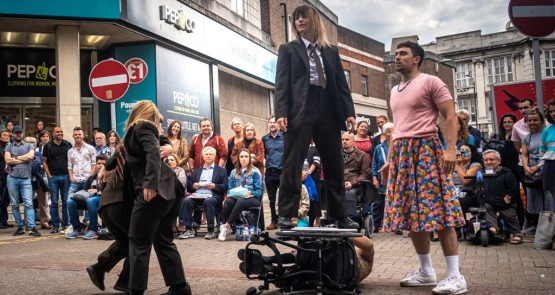 Outdoor performance of Frock, In the centre, Nadenh is lying on his side in his wheelchair. KJ is standing on the top wheel, wearing a black suit, white shirt and tie. To their left, two female dancers in black suits and ties are twisting around each other. To their left, Christian stands and looks at KJ, wearing a pink t-shirt and floral skirt.