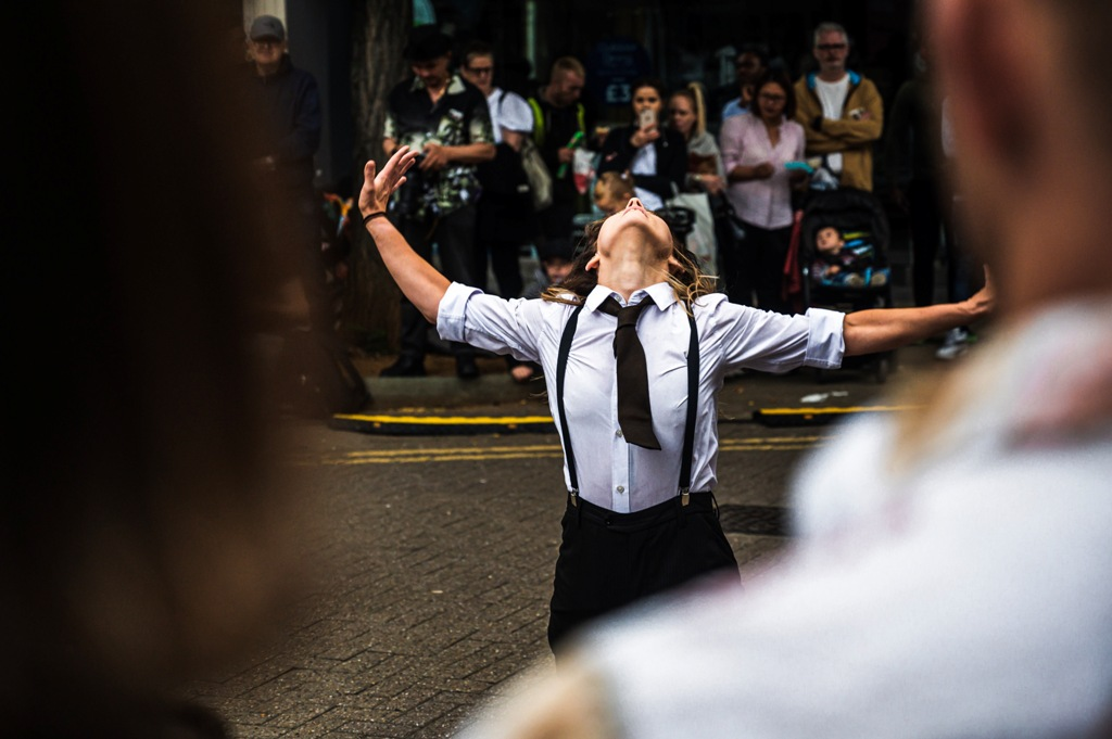 KJ at an outdoor performance of Frock, with her front to the camera. Wearing a white shirt, tie, suspenders and black trousers, she throws her arms wide to the side and bends far back, looking straight up to the sky. Behind her, the audience is watching.