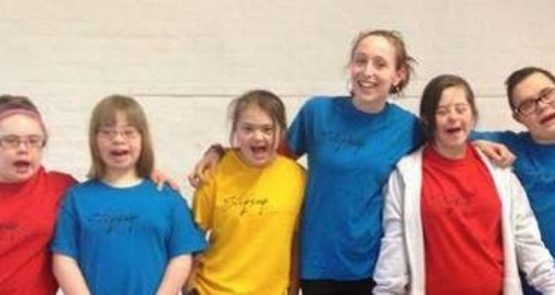 A group of youth dance company members in colourful t-shirts with their arms around each other and smiling into the camera