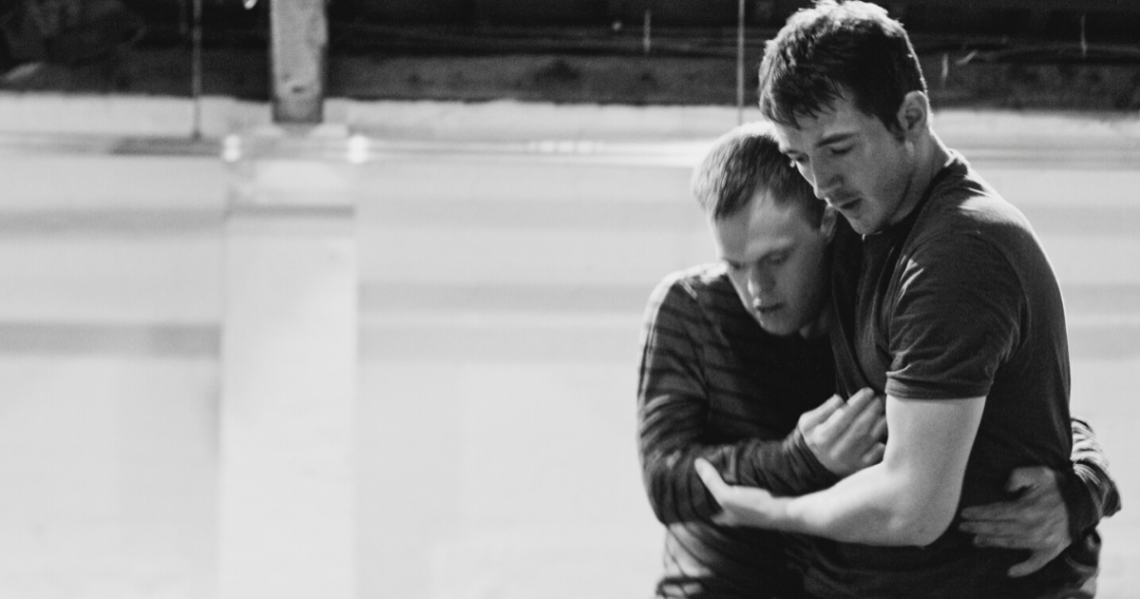 Black and white photo of male dancers Chris Pavia and David Willdridge in close embrace. They are side by side on the right side of the photo, one arm around each others' waist, the other arm held in front of their bodies; David's left hand gently cradling Chris's right elbow. Both are looking down, to a point on the floor in front of them.