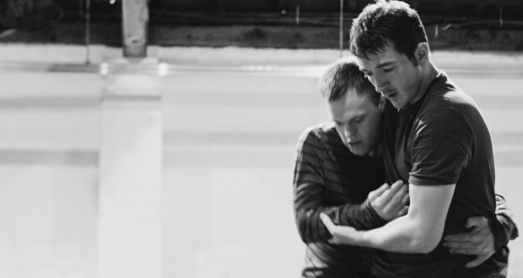 Black and white photo of two male dancers embracing.