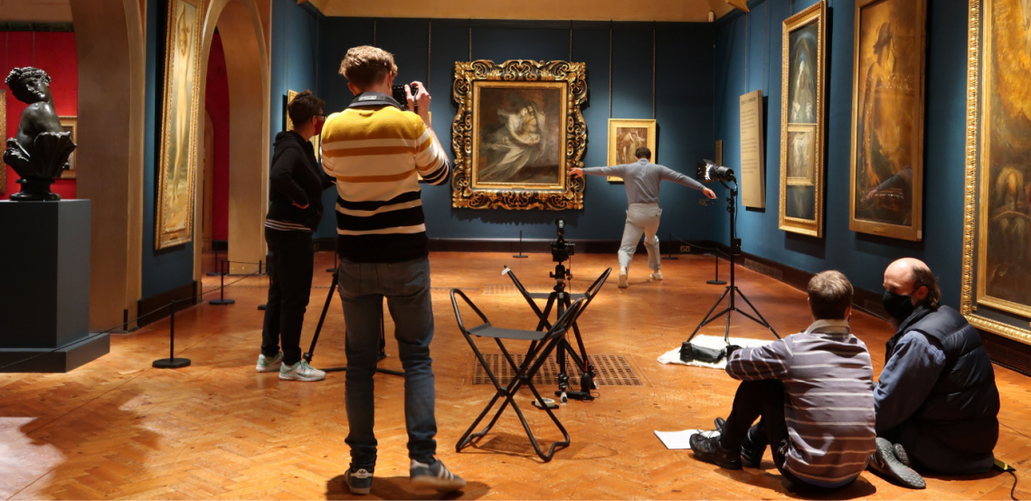 The team at Watts Gallery, in a large gallery space with dark blue walls and paintings hanging in elaborate golden frames. From left to right, Roz films and Callum photographs Christian as he dances in the background, Chris and Tom sit together on the floor in discussion.