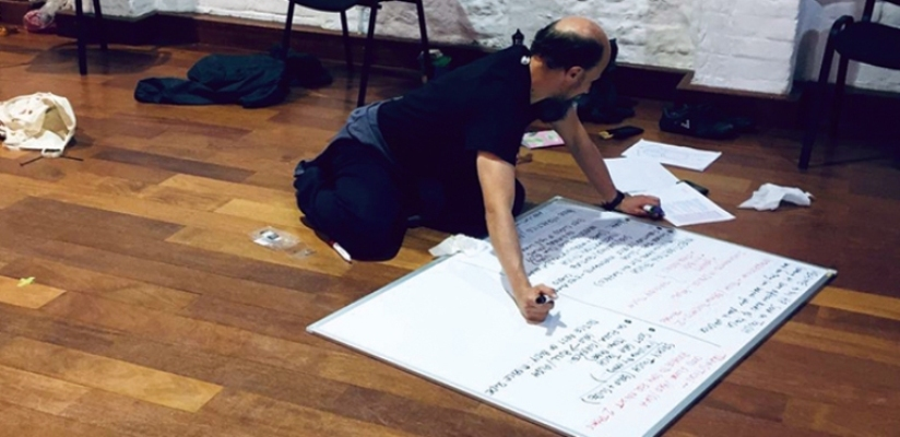 A photo of Tom Goodwin, kneeling on a wooden floor writing on a big whiteboard.