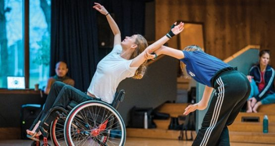 A wheelchair and a standing dancer dueting in the studio.