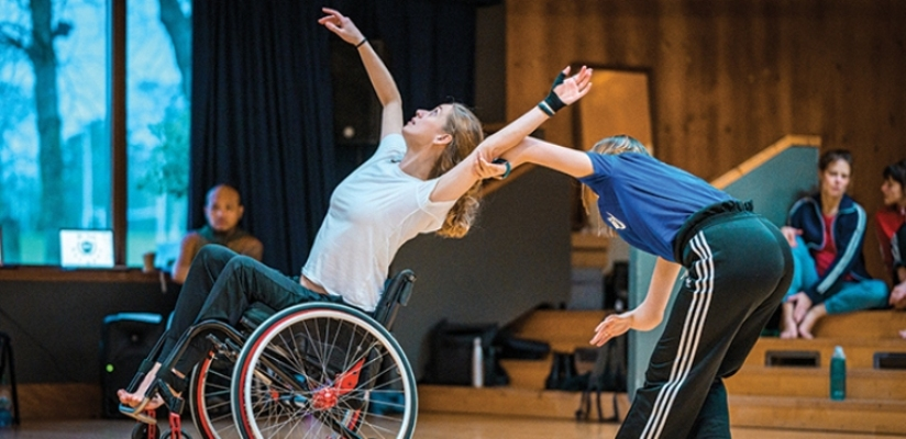 A duet of a wheelchair and a standing dancer in the studio. The wheelchair dancer is wearing a white t-shirt and black trousers. She is tipping back in her wheelchair with the front wheels lifting off the ground. She has her left arm stretched upwards. her right arm is moving upwards in a curve and she follows it with her gaze. The standing dancer is dressed in a blue t-shirt and black trousers with white stripes at the sides. They are bending forwards away from and with their back to the camera, holding the wheelchair dancer's left arm with their left hand. Both their upper arms are directly connected to their hands.