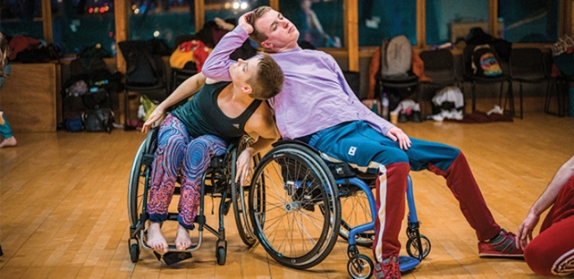 A duet of a female and a male wheelchair dancer leaning into each other. The male dancer is leaning casually back in his wheelchair, dressed in a lavender top, blue-red trousers and trainers. He is leaning with his right elbow on the female dancer's shoulders, his head tipped sideways into his hand. The female dancer is twisting around his upper arm, looking upwards to his hand. She is wearing a teal tank top and colourful patterned trousers. She is barefoot.