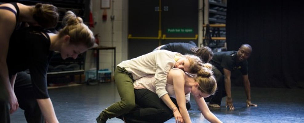 A pair of dancers, one crouching on the floor, the other relaxing over her shoulder and back
