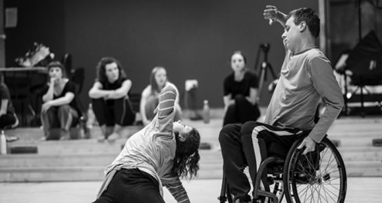 Black and white photo of a duet of a wheelchair dancer and a standing dancer.