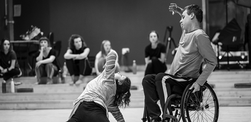 Black and white photo of a duet of a male wheelchair dancer and a female standing dancer. The wheelchair dancer is dressed in a long-sleeve top and dark trousers with white side stripes. he is holding on to the left wheel of his chair with his left hand. Hid right hand is lifted in front of his face, palm outwards. The female dancer is on the floor before him, only partly visible. She is wearing a white t-shirt over a striped top. She is leaning on her right arm, her back to the male dancer, and is twisting her body to the left, with her left elbow leading the movement. She is looking up, her dark hair floating over her shoulders.