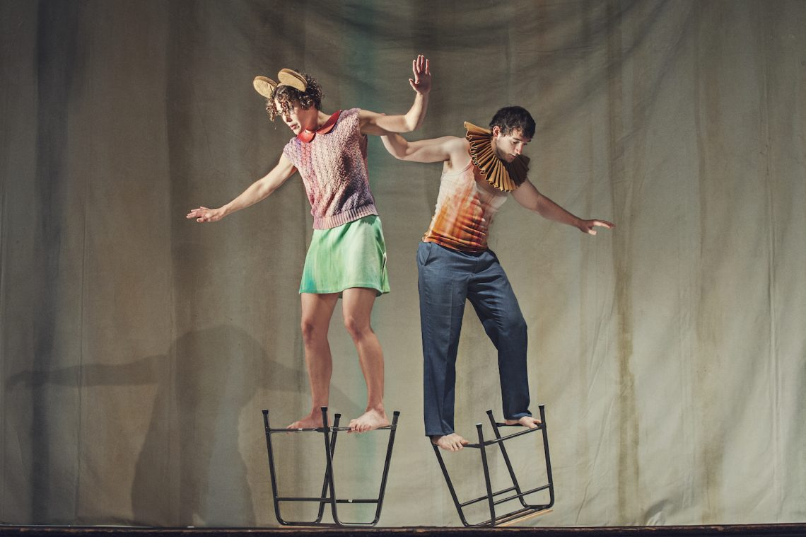 A photo from Artificial Things (2014) with two standing dancers balanced on upturned stools.