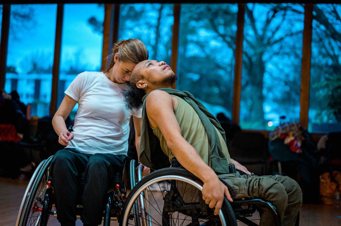 An image of Stopgap Dancer Nadenh and a wheelchair mentee working together in a studio