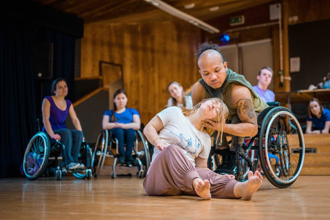 Stopgap dancers Nadenh and Hannah during a contact dance exercise. They are being looked on by Laura, and two other wheelchair dancers