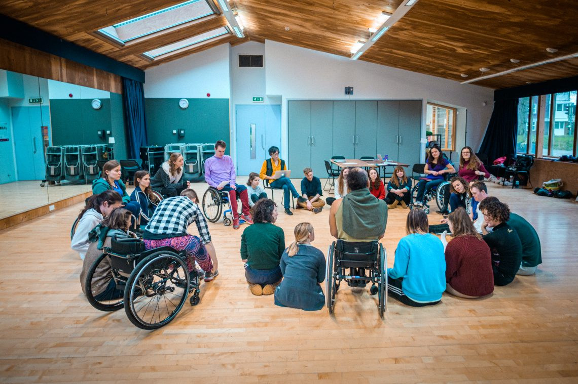 A group of people from Stopgap sat in a circle in a studio.