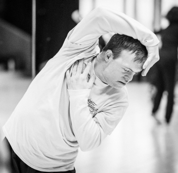A black and white photo of Chris Pavia dancing in the studio.