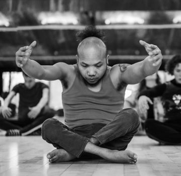 Black and white photo of Nadenh sat on the floor and dancing in the studio.