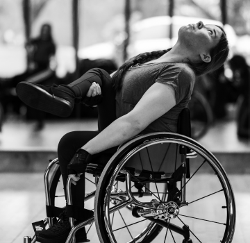 Black and white photo of Zelda, a wheelchair dancer, in the studio.
