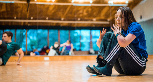 Annie-Rose, a disabled dancer, sits on the floor