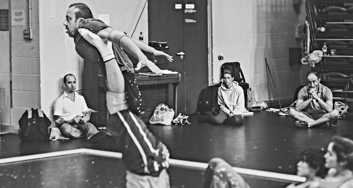 In the studio, Dave Toole flies in the air, suspended beneath the arms on someones legs.