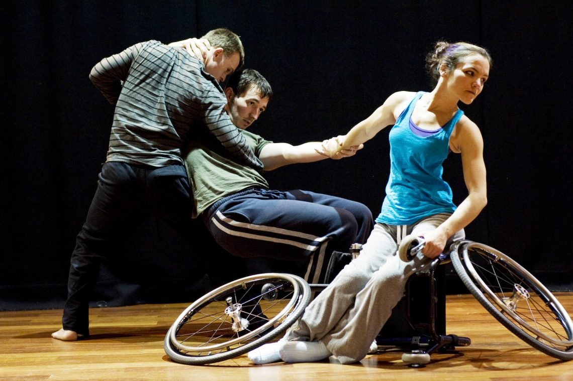 Laura, Chris and David in rehearsal. Laura sits on a dismantled wheelchair. Chris supports David as he sits without a chair between them.