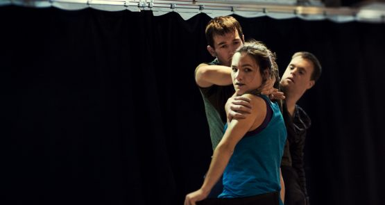 Laura, Chris and David in rehearsal. Laura peers at the camera over her shoulder, David and Chris are behind her
